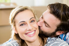 Young man kissing on womans cheek. Young men kissing on womans cheek at home Stock Photography