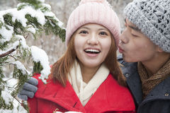 Young man kissing young woman in park in snow Royalty Free Stock Photo