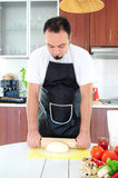 Young man in kitchen. Young man in apron in kitchen, rolling out dough Royalty Free Stock Photo
