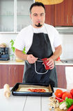 Young man in kitchen. Young man in apron in kitchen preparing pizza Royalty Free Stock Photography