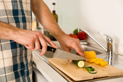 Time to cook. Young man on the kitchen cuting vegetables to cook Royalty Free Stock Images