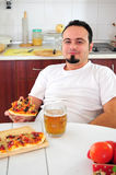 Young man in kitchen with homemade pizza. Young man in kitchen eating homemade pizza drinking beer Stock Images