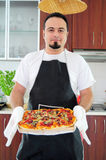 Young man in kitchen with homemade pizza. Young man in apron in kitchen with ready homemade pizza Stock Photography