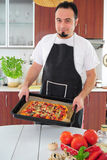Young man in kitchen with homemade pizza. Young man in apron in kitchen with ready homemade pizza Royalty Free Stock Photography