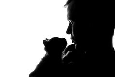 A young man with a kitten in his hands Stock Images