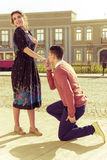 Young man kneeling and asking a girl to marry him in the park on royalty free stock photography