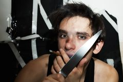 Young man with knife and cigarette Stock Photography