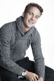 Young man in knit sweater and a smile. Beautiful young man in knit sweater and watch Royalty Free Stock Image