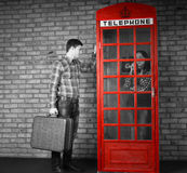 Young Man Knocking at the Telephone Booth Royalty Free Stock Photography