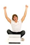 Young man with laptop. Casual guy sitting with laptop, arms raised Stock Photos