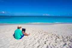 Young man with laptop on background of turquoise ocean Royalty Free Stock Photos