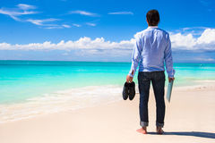 Young man with laptop on the background of turquoise ocean at tropical beach Stock Images