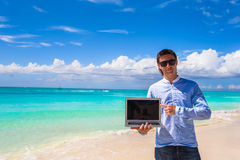 Young man with laptop on the background of turquoise ocean at tropical beach Royalty Free Stock Photography