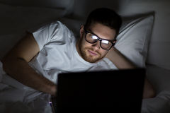 Young man with laptop in bed at home bedroom Royalty Free Stock Photography
