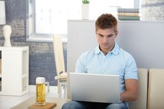 Young man with laptop and beer Royalty Free Stock Photography