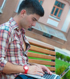 Young man with a laptop on the bench. stock image