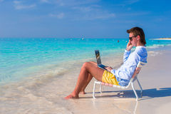 Young man with laptop and cell phone on tropical Stock Image