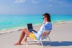 Young man with laptop and cell phone on tropical Royalty Free Stock Images