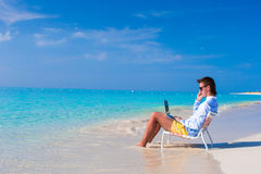 Young man with laptop and cell phone on tropical Royalty Free Stock Photography