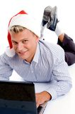 Young man with laptop and chritsmas hat Stock Photography