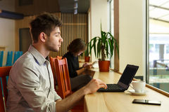 Young man with laptop in city cafe, freelancer. Morning in modern city, youth lifestyle. Young man looks on screen of laptop, work in public place, sitting Stock Photography