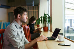 Young man with laptop in city cafe, freelancer. Morning in city cafe, youth lifestyle. Young man looks on screen of laptop, work in public place, sitting indoor Royalty Free Stock Image