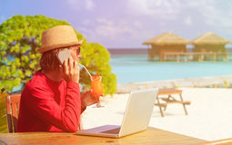 Young man with laptop and cocktail at beach Royalty Free Stock Photo