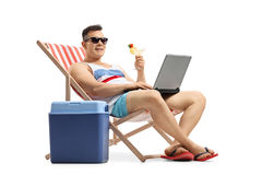 Young man with laptop and cocktail sitting in a deck chair Stock Photos