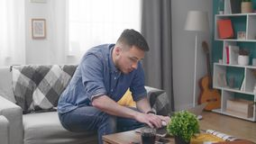Young man with laptop computer calling on smartphone at home.  stock footage