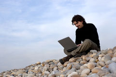 Young man with laptop computer in the outdoors Stock Images