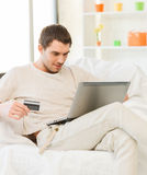 Young man with laptop and credit card at home Stock Photography
