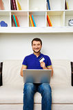 Young man with laptop and credit card at home Stock Images