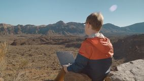 A young man with a laptop surrounded by mountainous volcanic landscape stock video