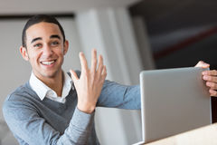 Young man with laptop gesturing and smiling. Young black worker in grey sweater sitting in office, holding laptop, looking at camera, smiling and gesturing. Copy Stock Image