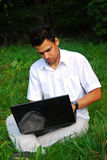 Young man with laptop on the grass. Young man in white shirt working with laptop sitting on the grass in park Stock Image