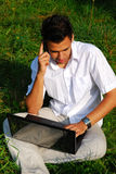 Young man with laptop on the grass. Young man in white shirt talking by phone and  working with laptop sitting on the grass in park Stock Photography