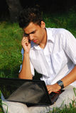 Young man with laptop on the grass. Young man in white shirt talking by phone and  working with laptop sitting on the grass in park Royalty Free Stock Image