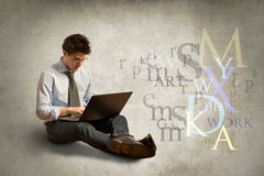 Young man with laptop. On gray wall background Royalty Free Stock Photography
