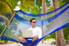 Young man with laptop at hammock on tropical vacation royalty free stock photography