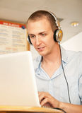 Young Man with Laptop and Headphones Stock Photo