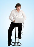 Young man with laptop and headphones Stock Photography