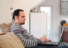 Young man with laptop at home Stock Image
