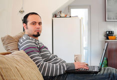 Young man with laptop at home. Young man with laptop sitting on the sofa at home Stock Photography