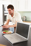 Young Man With Laptop In Kitchen Royalty Free Stock Photo