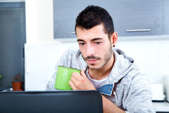 Young man with laptop in the kitchen Royalty Free Stock Image