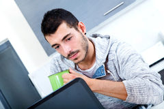 Young man with laptop in the kitchen Royalty Free Stock Photography
