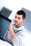 Young man with laptop in the kitchen Stock Photography