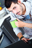 Young man with laptop in the kitchen Stock Images