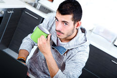 Young man with laptop in the kitchen Stock Image