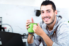 Young man with laptop in the kitchen Stock Photo